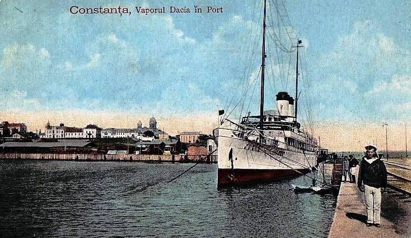 """Nava """"Dacia"""" în portul Constanța. În plan îndepărtat se văd turlele catedralei """"Sf Apostoli Petru și Pavel""""."""