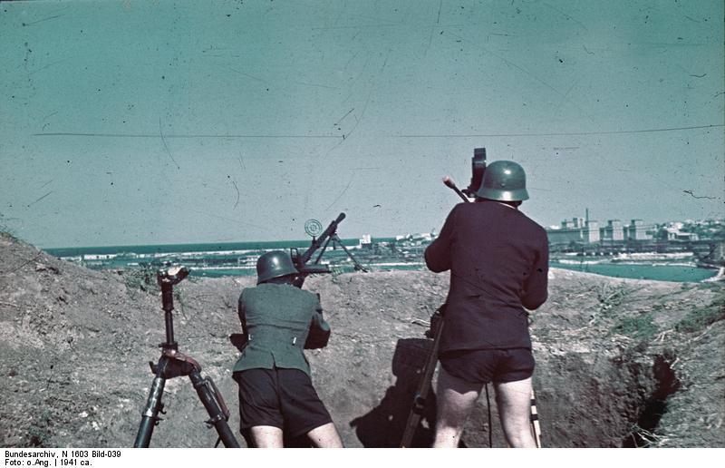 Cubi de mitralieră amplasat pe malul portului Constanța. În plan îndepărtat se văd silozurile portului.