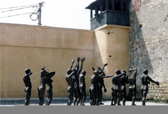 """O lucrare de amploare prin dimensiune şi suflu artistic, grupul statuar """"Cortegiul Sacrificaţilor"""" de Aurel Vlad, care tinde să devină una dintre emblemele muzeului. Este vorba de optsprezece siluete umane, mergând spre un zid care le închide orizontul, aşa cum comunismul zăgăzuise viaţa a milioane de oameni. Prezentată în 1997 în lemn, lucrarea a fost turnată în anul următor în bronz şi este amplasată azi într-o altă curte interioară a fostei închisori. Este punctul preferat unde sute şi mii de turişti se fotografiază la trecerea prin Memorialul de la Sighet."""