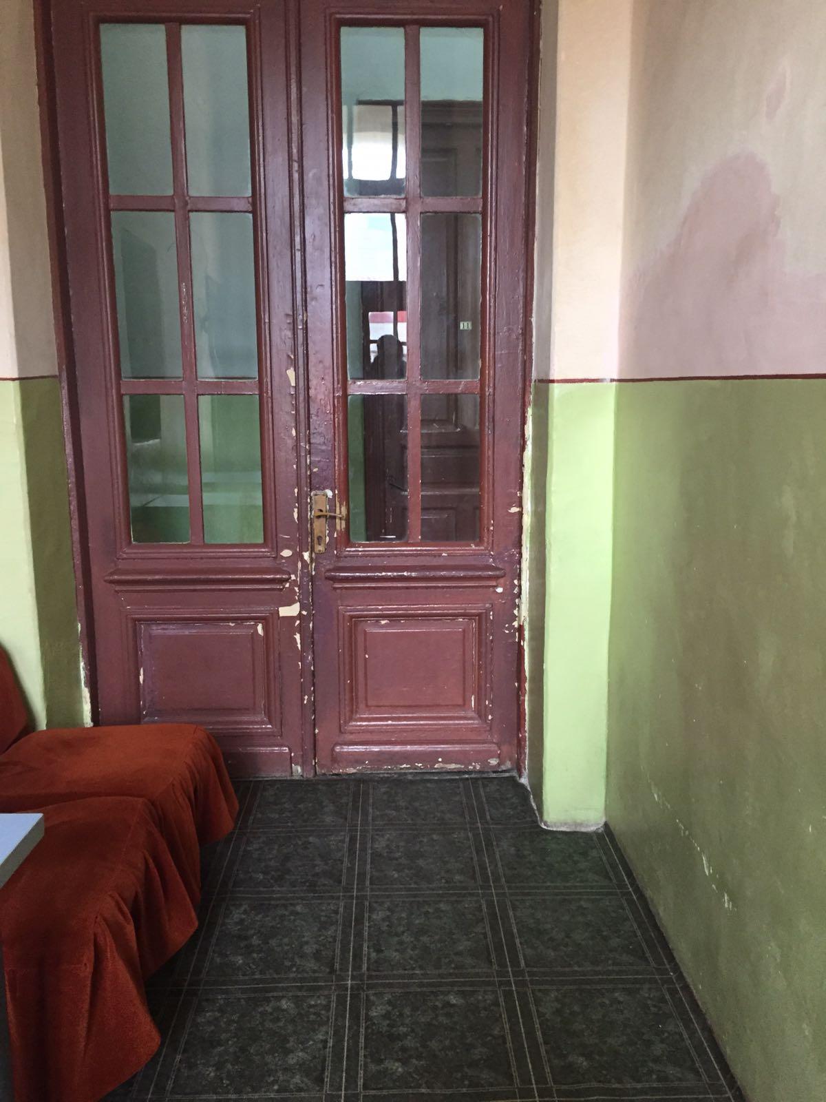 Ușa din spatele clădirii de patrimoniu, cu acces în curtea din spate. Este o ușă de școală europeană, reprezentativă pentru puturoșenia conducerii Colegiului, în care Anamaria Ciobotaru este cea dintâi și unica prof. asistent univ. Doctor
